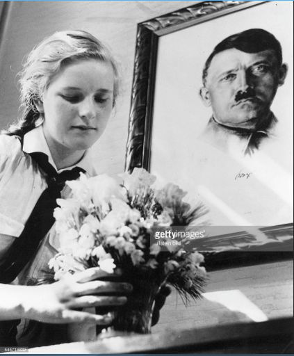 Freshly picked flowers are placed on the table in front of der Führer's portrait